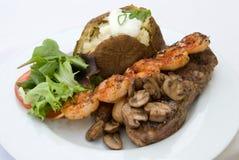 Stake and Shrimp Dinner. Gourmet dinner of Steak, grilled shrimp, mushrooms, loaded baked potato and mixed greens Stock Photo