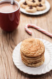 Stake of snickerdoodle cookies and hot chocolate. Plate of snickerdoodle cookies, hot chocolate, peppermint candy cane, and chocolate peanut blossom cookies on Stock Image