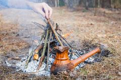 At the stake in the spring forest, a clay Turkish coffee pot is heated against the grass. In the frame one man`s hand. stock photography