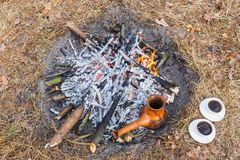 At the stake in the spring forest, a clay Turkish coffee pot is heated against the grass. stock photo