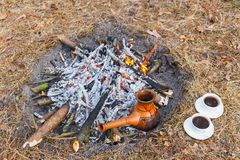 At the stake in the spring forest, a clay Turkish coffee pot is heated against the grass. stock photos
