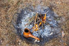 At the stake in the spring forest, a clay Turkish coffee pot is heated against the grass royalty free stock image