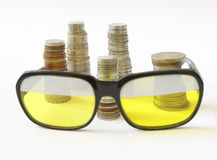 Stakes of coins and old style sunglasses Royalty Free Stock Images
