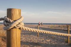 Stakes with rope on the beach at sunset Royalty Free Stock Photography