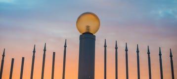 Staket med skarpa maxima och gatalampa i aftonen Gatalampa på bakgrunden av en härlig solnedgånghimmel royaltyfri bild