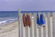 Staket med strandhanddukar på stranden royaltyfri bild