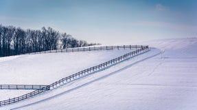 Staket på en snö täckte lantgårdfältet i lantliga Carroll County, Mars royaltyfri foto