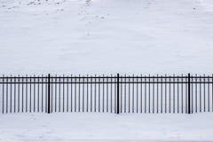 Staket som göras av gjutjärngaller och granitkolonner i molnigt snöig väder Arkivbilder