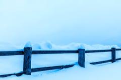 Staketet eller häcken och högarna av insnöat bygden eller i byn i den kalla vinterdagen royaltyfria bilder