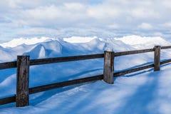 Staketet eller häcken och högarna av insnöat bygden eller i byn i den kalla vinterdagen arkivfoton