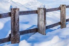 Staketet eller häcken och högarna av insnöat bygden eller i byn i den kalla vinterdagen royaltyfria foton