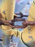 Staketpoler för Chain sammanlänkning låste rostig metall för målarfärg för skalning för rostgrungeguling Fotografering för Bildbyråer