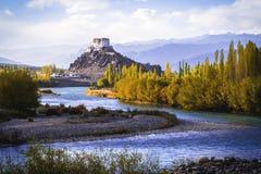 Stakna Gompa y río Indo antes de la puesta del sol con el cielo nublado y las montañas Imágenes de archivo libres de regalías