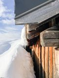 Stalactite on a chalet in the mountain. A chalet in the mountain with stalactite and snow, blue sky royalty free stock images