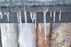 Stalactites. Frozen water creating stalactites on a wooden roof royalty free stock photos