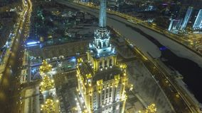 Stalin high rise building Moscow. Modern luxury hotel Ukraine Downtown. Business skyscrapers. Winter snow and ice river. Night. Aerial drone Fpv from above view stock video