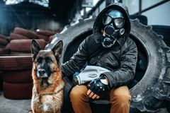 Stalker in gas mask and dog, post-apocalypse. Stalker in gas mask and dog, friends in post apocalyptic world. Post-apocalypse lifestyle on ruins, doomsday Royalty Free Stock Photo