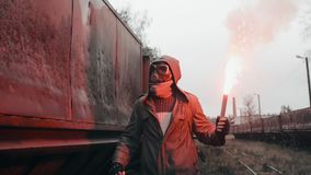 Stalker in gas mask walks through abandoned train carriages with fire in hand