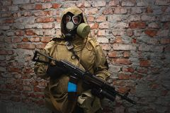 Stalker in gas mask with weapon near the brick wall. Background royalty free stock images