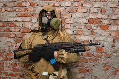 Stalker in gas mask with weapon near the wall. Stalker in gas mask with weapon near the brick wall royalty free stock images