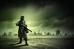 Stalker with gun. Man in gas mask and camouflage holding gun. Disaster concept Stock Image