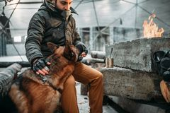 Stalker, post-apocalypse soldier feeding a dog. Post apocalyptic lifestyle on ruins, doomsday, judgment day Stock Photo