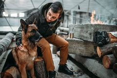 Stalker, post-apocalypse soldier feeding a dog. Post apocalyptic lifestyle on ruins, doomsday, judgment day Royalty Free Stock Images