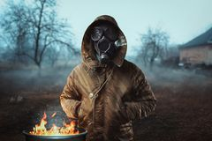 Stalker soldier in gas mask against fire, doomsday. Stalker soldier in gas mask against fire, survivor man after nuclear war. Post apocalyptic lifestyle Royalty Free Stock Images