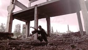 Stalker survivalist with a crossbow and found things sneaks through the ruins looking around. eg presleduet someone. He`s careful. Post-apocalyptic landscape stock footage