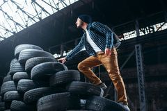 Stalker, traveler climbs a mountain of tires. Abandoned factory. Danger zone, deserted place Stock Image
