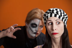 Stalking Woman. Woman is stalked by another in scary makeup Stock Photo