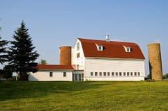 Stall mit rotem Gambrel Dach und Silos Stockfotografie