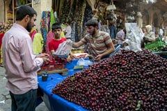 A stall selling cherries in Urfa in Turkey. A shop keeper weighs a bag of cherries in the Urfa (Sanliurfa) bazaar in south eastern Turkey Stock Image