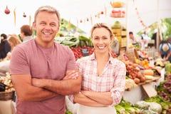 Stalla di funzionamento delle coppie al mercato dell'alimento fresco degli agricoltori Fotografia Stock Libera da Diritti