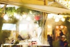 Stalle traditionnelle de Noël au marché de nouvelle année et de Noël avec des lumières, décorations, cuves avec les thés chauds,  images stock