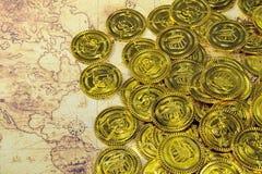 Stalowa czaszki i pirata złota moneta na stary świat mapie Fotografia Stock