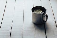 Stalowa filiżanka herbata z plasterkiem cytryna na białego rocznika drewnianym tle Obraz Royalty Free