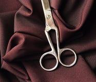 Stalowi nożyce na Burgundy tkaninie Zdjęcia Royalty Free