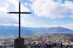 Stalowy chrześcijanina krzyż na górze góry i miasto krajobrazu piękny pejzaż miejski Włochy obraz stock