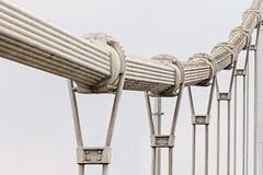Stalowy gęsty kręcony zawieszenie mostu kabel z liczbą metal zapętla przeciw białemu nieba tłu iść w odległość obraz stock