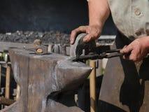 Stalowy kowadło, kurenda gładzi kamień w ręce na górze którego kłama gorącego workpiece który trzyma parą cążki, obrazy stock