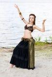 Stam- amerikansk stildansare för ung kvinna Flickadans och posera på dräkten för magdans för strandsand den bärande ethnic arkivbild