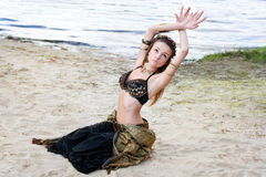 Stam- amerikansk stildansare för ung kvinna Flickadans och posera på dräkten för magdans för strandsand den bärande ethnic royaltyfria bilder