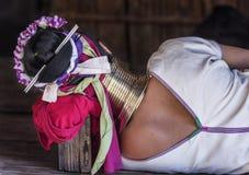 Stam- dam för lång hals som sover på golv genom att använda en träsnitt som kudden i Chiang Mai den långa halsbyn, Chiang Mai, Th Royaltyfri Foto