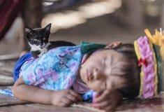 Stam- flicka för lång hals som tillbaka sover på golv, och hennes älsklings- kattsammanträde på henne, Chiang Mai, Thailand royaltyfri bild