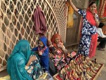 Stam- kvinnor säljer traditionella färgglade skor för ungar royaltyfri fotografi