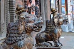 Stammen mythische leeuwstandbeelden in oude stad van Katmandu, Nepal Royalty-vrije Stock Foto's