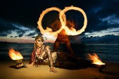 Stammes- Artmädchen auf einem tropischen Strand mit Feuer bei Sonnenuntergang Stockbild