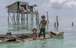 Stammes- Kinder Bajau, die Spaß durch das Springen in Meer von ihrem Boot, Sabah Semporna, Malaysia haben Stockbilder