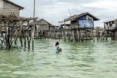 Stammes- Mädchen Bajau, das ihren Bruder zu ihrem Haus trägt, bevor er in das Meer gesunken erhält, Sabah Semporna, Malaysia Stockfoto